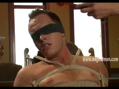 Blindfolded and gagged young gay guy gets his cock roughly jerked off by a dominatig man