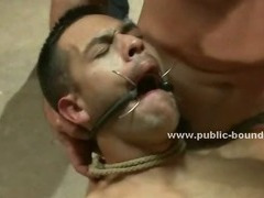 Blindfolded stud with a mouth stretcher is tied up and forced to suck a bunch of horny dicks