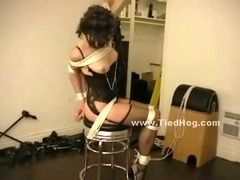 Gagged whore in fishnet stockings is tied up and has her ass flogged by a man