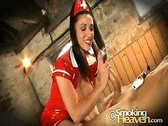 Smoking nurse in latex giving  a hand job