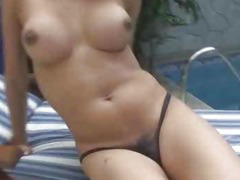 Foxy blonde shemale tugging her cock by the pool