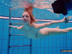 Redhead honey swimming nude in the pool