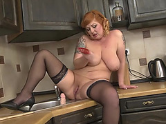 Thick redheaded mama copulates a large fake penis lazily