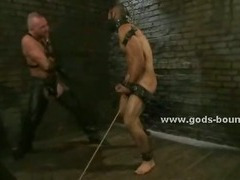 Man in ropes and blindfolded is tied from pole and abused by master and slave in threesome bdsm sex